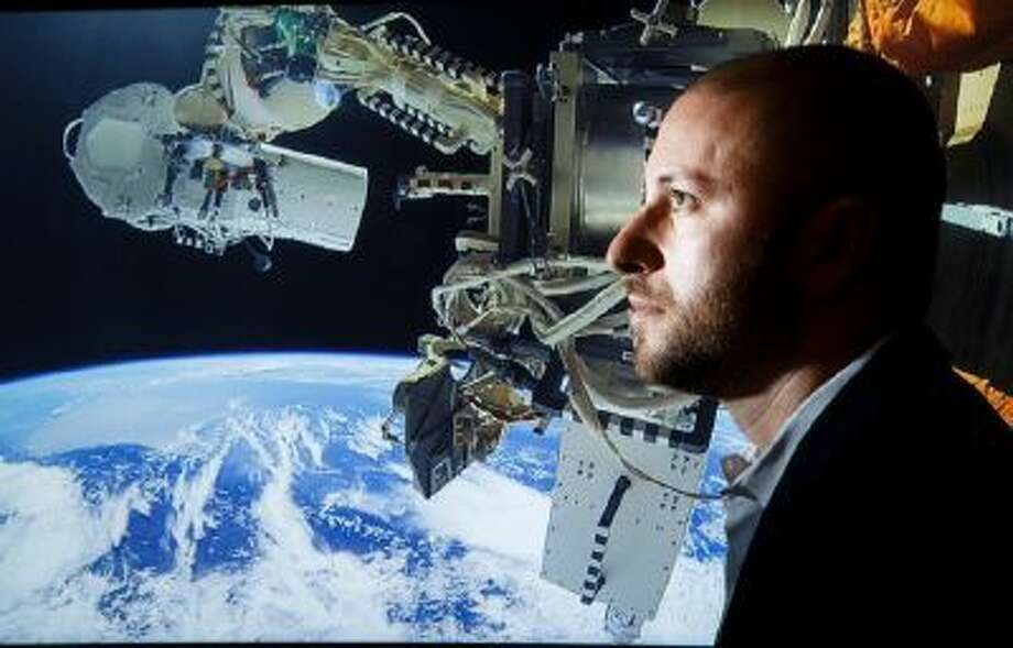 A portrait of Dan Lopez, director of technology for UrtheCast, poses with a picture of the company's two video cameras attached to the International Space Station.
