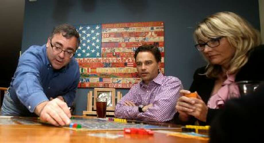 In this photo taken Thursday, Jan. 9, 2014, Spirit Airlines CEO Ben Baldanza left, Ted Christie, center, the airline's chief financial officer, and DeAnne Gabel, right, director Investor relations, right, play a game of Power Grid at Baldanza's home, in Fort Lauderdale, Fla.
