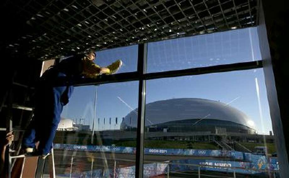 A worker at the Ice Cube Curling Center cleans a window with a view of the Bolshoy Ice Dome during final preparations for the 2014 Winter Olympics in Sochi, Russia. Photo: AP / AP