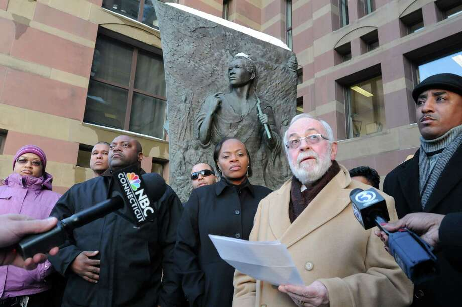 Attorney John Williams, second from right, reads a statement outlining concerns for a group of African-American New Haven police officers outside New Haven City Hall, by the Amistad Memorial, Thursday. Photo: Mara Lavitt — New Haven Register       / Mara Lavitt
