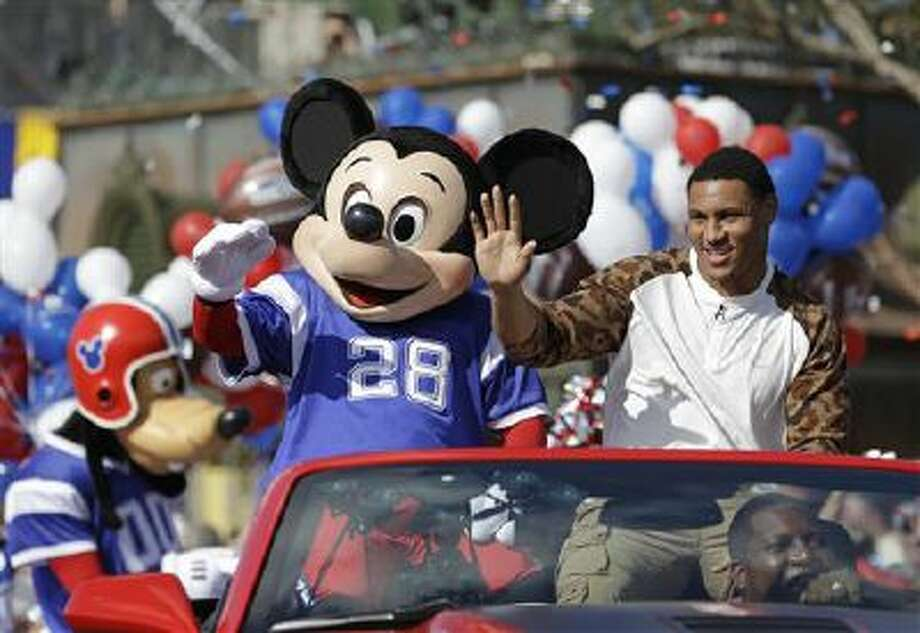 The 2014 Super Bowl MVP Malcolm Smith a Seattle Seahawks linebacker, waves to spectators as he rides in a parade at Walt Disney World with Mickey Mouse in Lake Buena Vista, Fla. Photo: AP / AP