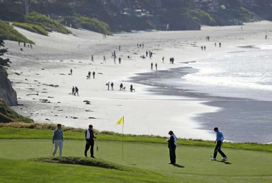 Roberto Castro, right, walks to his ball on the tenth green of the Pebble Beach Golf Links during a practice round of the AT&T Pebble Beach Pro-Am golf tournament in Pebble Beach, Calif., before the 2013 tournament.
