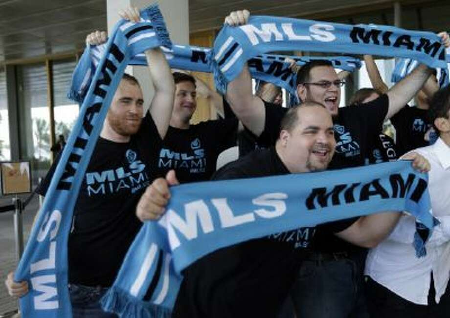 Fans from the Southern Legion soccer supporters hold up scarves before a news conference where former England soccer star David Beckham announced he will exercise his option to purchase a Major League Soccer expansion team in Miami, Wednesday, Feb. 5, 2014, in Miami.