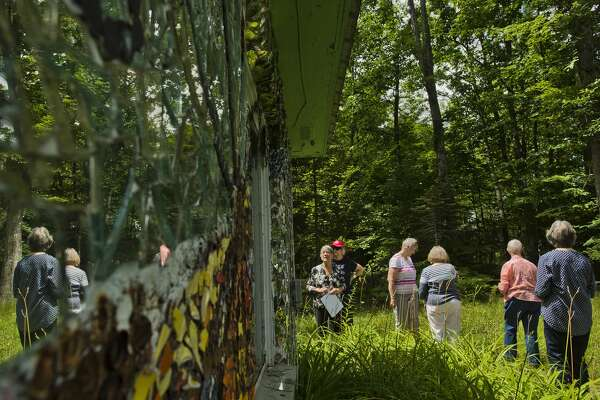 A tour group from Creative 360 checks out the John Pratt Mosaic House at 102 E. Isabella Road on Tuesday, July 25, 2017. Artist John Pratt covered the home, which he grew up  in, with mosaic murals made of broken pieces of pottery, china and  mirrors.