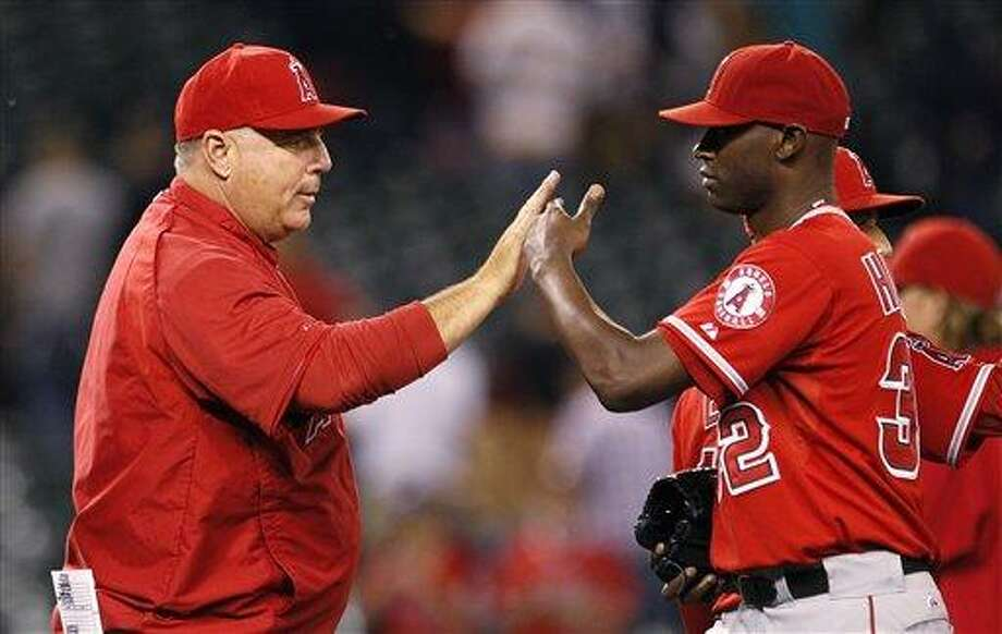 Los Angeles Angels manager Mike Scioscia, left, greets closer LaTroy Hawkins after the team beat the Seattle Mariners in a baseball game Friday, Aug. 31, 2012, in Seattle. The Angels won 9-1. (AP Photo/Elaine Thompson) Photo: ASSOCIATED PRESS / AP2012