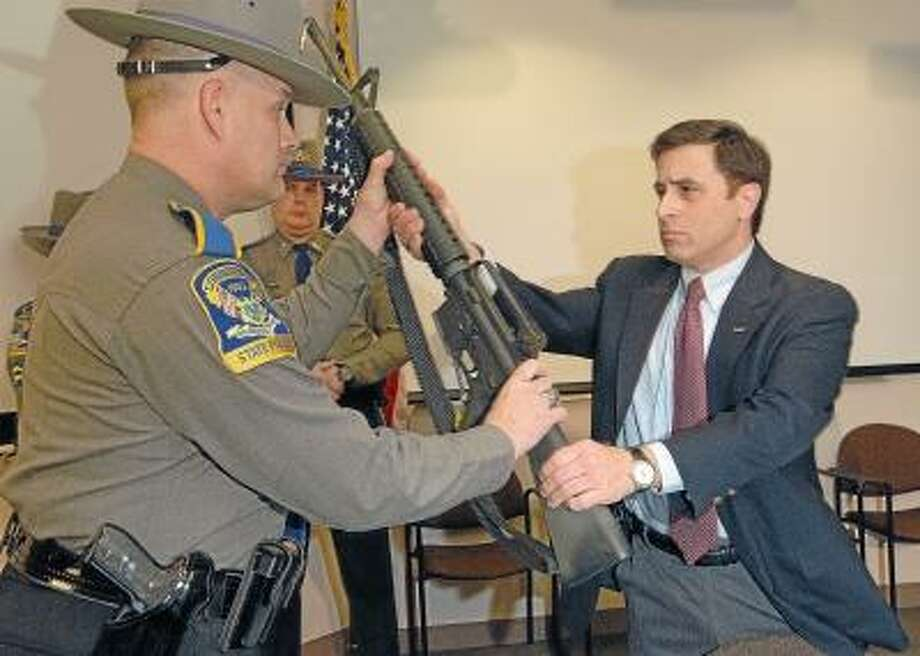 Catherine Avalone/The Middletown Press Moved by the Sandy Hook Elementary School shooting, Cheshire resident Joe Bango turns over his AR-15 and magazine to Lt. Eric Cooke of the Connecticut State Police at a press conference held by Congresswoman Rosa DeLauro, CT-3 as a part of the SAFER (Support Assault Firearm Elimination and Education for our) Streets Act which provides gun owners with a tax credit if they choose to turn in an assault weapon. Bango retired in 2005 from the U.S. Navy Reserves where he served with the Seabees and Naval Intelligence.