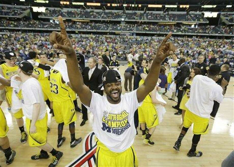 Michigan's Eso Akunne celebrates after a regional final game against Florida in the NCAA college basketball tournament, Sunday, March 31, 2013, in Arlington, Texas. Michigan won 79-59 to advance to the Final Four. (AP Photo/David J. Phillip) Photo: AP / AP