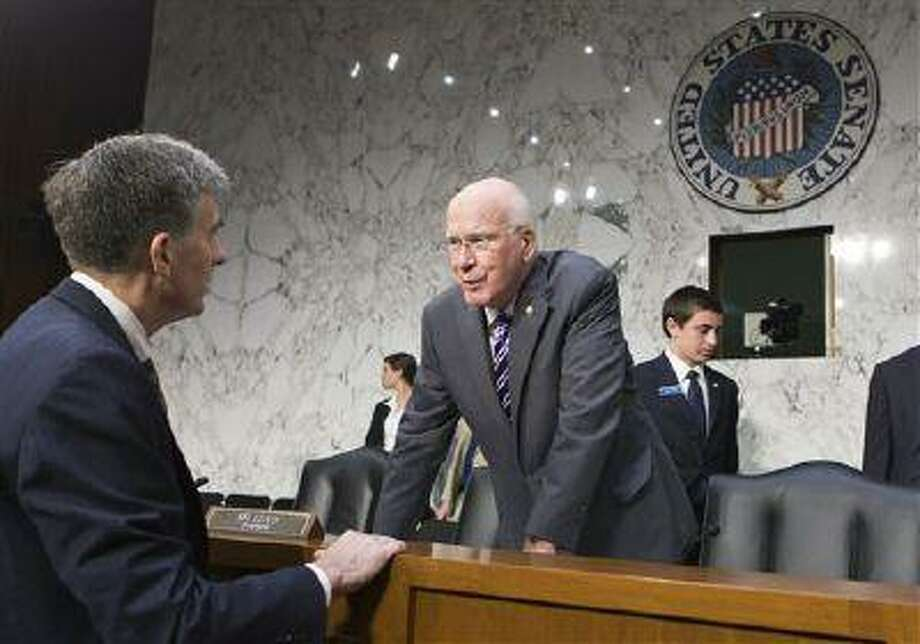 Senate Judiciary Committee Chairman Sen. Patrick Leahy, D-Vt., center, leans over the dais to speak with Chris Inglis, left, deputy director of the National Security Agency, after he and other national security officials testified about the NSA's surveillance programs. Photo: AP / AP