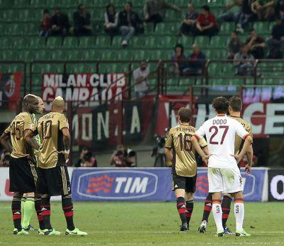 FILE - In this May 12, 2013, file photo AC Milan players Mario Balotelli, left, Kevin Prince Boateng (10) stand on the pitch during a stoppage in play in a Serie A soccer match between AC Milan and AS Roma, at Milan's San Siro Stadium. The game was stopped for almost two minutes because of racial abuse by Roma fans towards Balotelli and Boateng. Photo: AP / AP