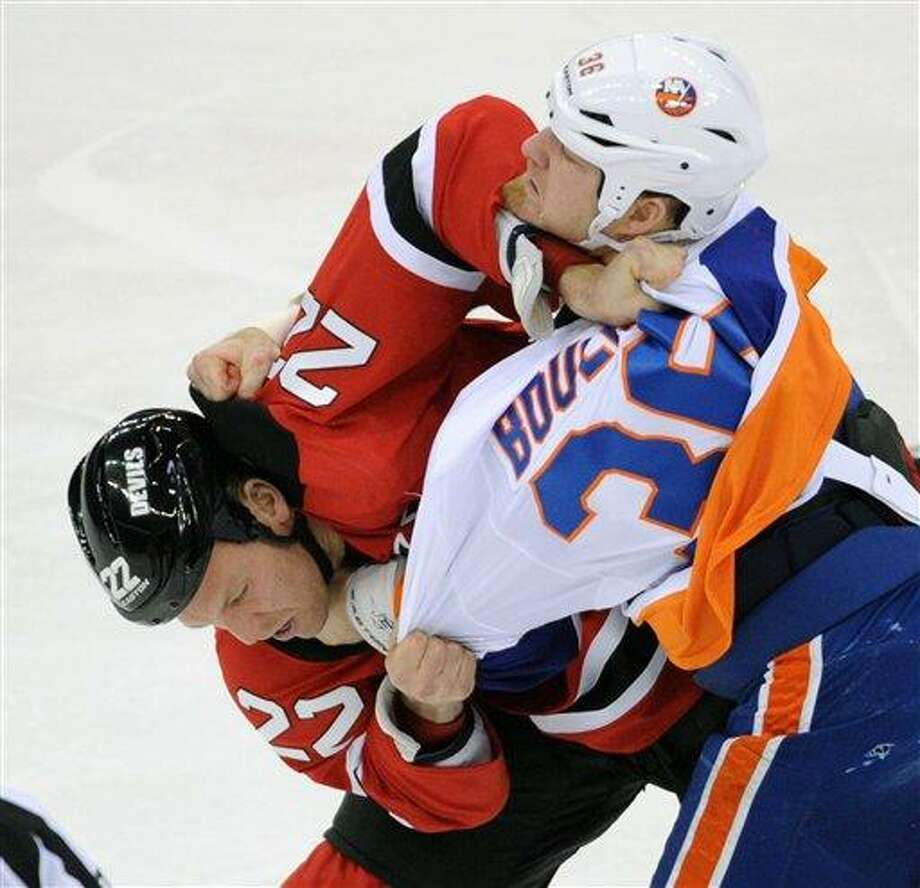 New Jersey Devils' Krystofer Barch, left, and New York Islanders' Eric Boulton fight during the first period of an NHL hockey game Thursday, Jan. 31, 2013, in Newark, N.J. (AP Photo/Bill Kostroun) Photo: AP / FR51951 AP