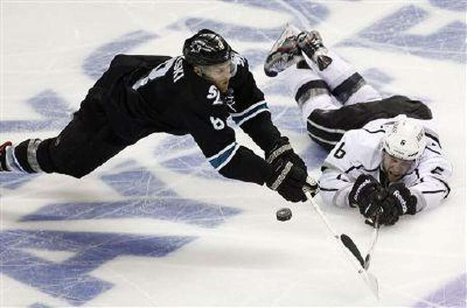 San Jose Sharks center Joe Pavelski (8) battles for a puck against Los Angeles Kings defenseman Jake Muzzin (6) during the third period in Game 6 in San Jose, Calif., May 26, 2013. Photo: AP / FR155217 AP