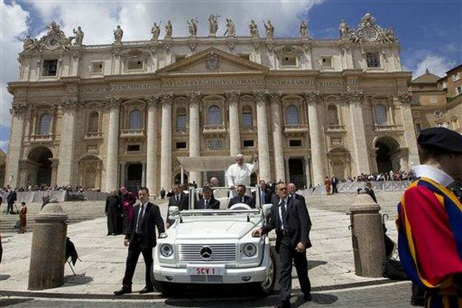 Pope Francis waves as he leaves at the end of his weekly general audience, in St. Peter's Square, at the Vatican, Wednesday, May 29, 2013. The rain hasn't stopped Pope Francis. The 76-year-old pontiff, who lost part of a lung during his youth to an infection, got soaked Wednesday as he braved a brief spring shower to kiss babies and greet crowds at his weekly general audience in St. Peter's Square. Zooming around the piazza in his open-air jeep, Francis had no umbrella or cover over him as he made his way through a sea of brightly colored umbrellas, happily stopping to caress and kiss babies handed up to him. (AP Photo/Andrew Medichini) Photo: AP / AP