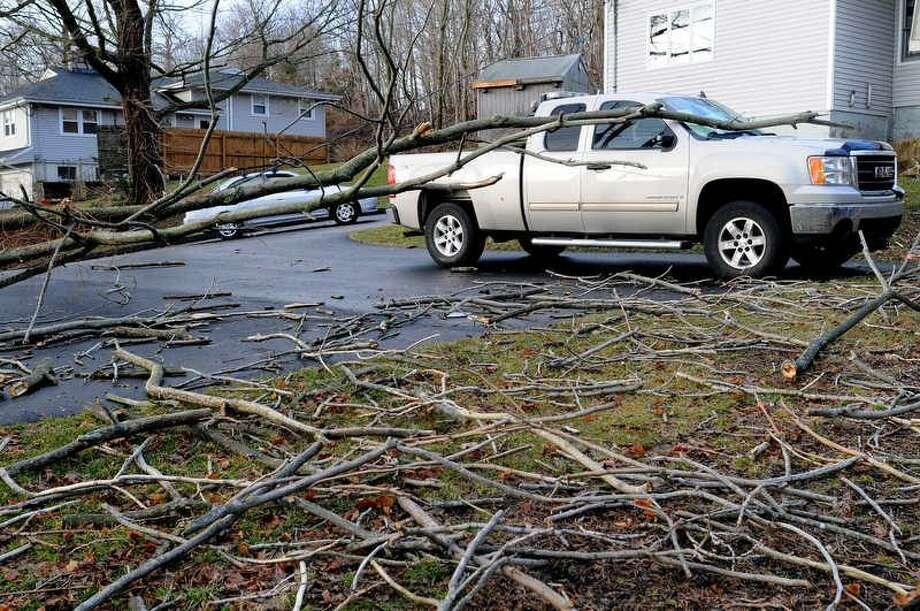 High winds during the night caused a tree in East Haven to fall on a pickup truck while pulling down the power line from the house causing it to dangle dangerously close to traffic on High Street Thursday morning. Photo by Peter Hvizdak / New Haven Register Photo: New Haven Register / ©Peter Hvizdak /  New Haven Register