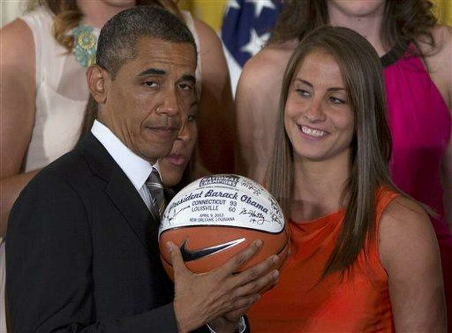 University of Connecticut Huskies basketball guard Caroline Doty looks at President Barack Obama as he shows the signed basketball she just gave him during a ceremony in the East Room of the White House in Washington, Wednesday, July 31, 2013, where the president honored the 2013 NCAA Women's Basketball Champion team, the  University of Connecticut Huskies. (AP Photo/Carolyn Kaster) Photo: AP / AP
