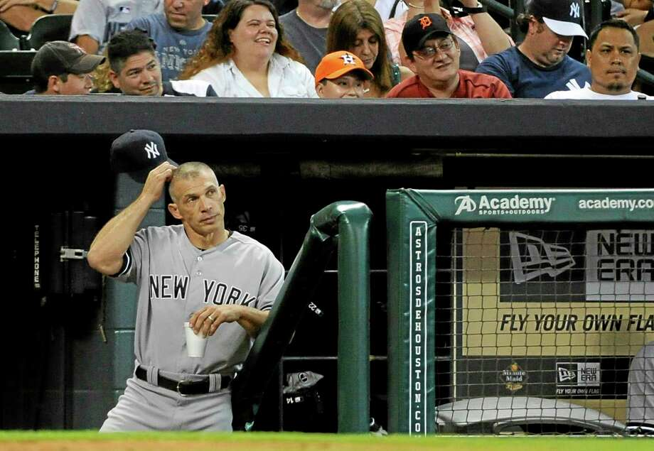 Yankees manager Joe Girardi scratches his head as he stands in the dugout in the 13th inning Sunday. Photo: Pat Sullivan — The Associated Press   / AP