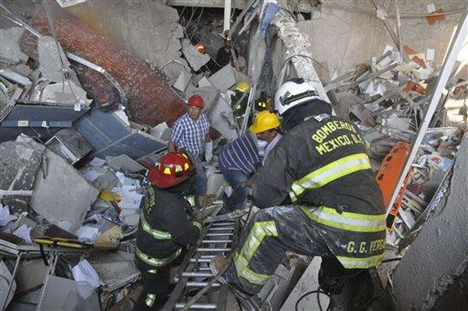 Firefighters belonging to the Tacubaya sector and workers dig for survivors after an explosion at an adjacent building to the executive tower of Mexico's state-owned oil company PEMEX, in Mexico City, Thursday Jan. 31, 2013. A large explosion occurred in the lower floors of the building and dozens have been reported injured so far. (AP Photo/Guillermo Gutierrez) Photo: AP / AP
