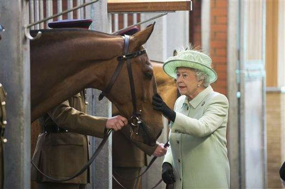 Britain's Queen Elizabeth II strokes the nose of Harlequin as she meets members of the King's Troop Royal Horse Artillery during her visit to Royal Artillery Barracks in London, Friday May 31, 2013. The King's Troop are a mounted, ceremonial unit that fires gun salutes on royal anniversaries and state occasions. (AP Photo/Paul Grover,Pool) Photo: AP / POOL Daily Telegraph