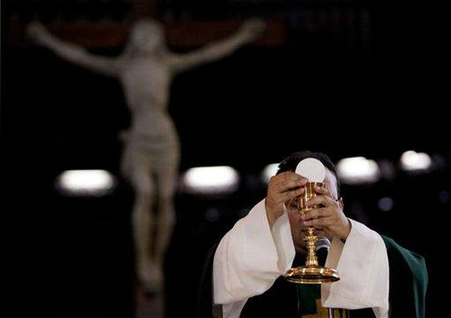 In this May 29, 2013 photo, a priest blesses the wine and bread as he celebrates Mass at a Catholic church in Caracas, Venezuela. Church officials say food shortages and foreign exchange restrictions are causing a lack of ingredients needed to celebrate Mass: altar wine as well as wheat to produce communion wafers. Venezuela has maintained strict currency controls since 2003, creating a black market that now sells dollars at more than triple the official rate of 6.3 bolivars. Falling oil exports and foreign investment have helped dry up the dollar supply.  (AP Photo/Fernando Llano) Photo: AP / AP