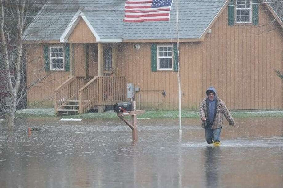 "Dispatch Staff Photo by JOHN HAEGER <a href=""http://twitter.com/oneidaphoto"">twitter.com/oneidaphoto</a> A man makes his way along Waterview in the Village of Sylvan Beach as flood waters rise on Thursday. Photo: Oneida Daily Dispatch / Oneida Daily Dispatch"