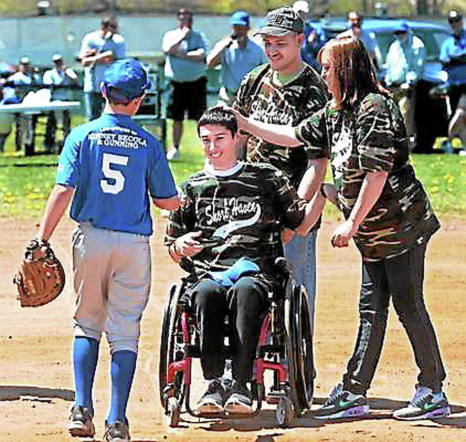 fILE PHOTO: Army Ranger Spc. First Class Sean Pesce of West Haven, who was injured in Afghanistan, came home from rehabilitation at the Boston VA to a welcome at the first day of Shore Haven Junior League baseball. Pesce threw out the first pitch which was returned to him by Robert Forleo, age 11 of West Haven. Sean's dad, Dan, and mom, Gail, are with him. Mara Lavitt/New Haven Register Photo: Journal Register Co.