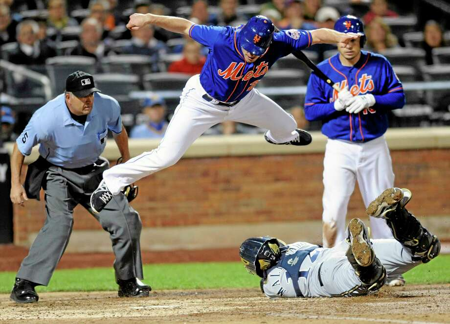 The Mets' Daniel Murphy jumps over Milwaukee Brewers catcher Martin Maldonado attempting to score as umpire Dale Scott, left, and batter Travis d'Arnaud, right, look on during the sixth inning of Friday's game in New York. Murphy was tagged out after he didn't touch the plate. Photo: Bill Kostroun — The Associated Press   / FR51951 AP
