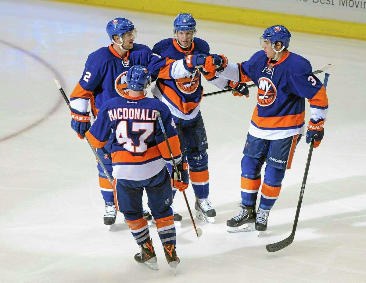 New York Islanders' Josh Bailey (12) celebrates his goal against the Nashville Predators with Andrew MacDonald (47), Peter Regin (16) and Travis Hamonic (3) in the third period of a preseason game Friday in Uniondale, N.Y. The Islanders won 6-4.