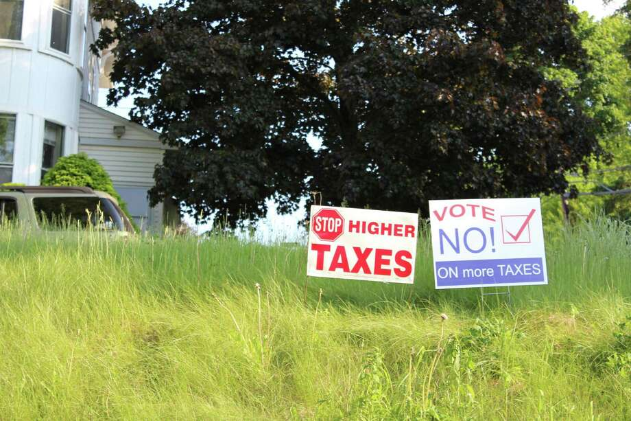 JASON SIEDZIK/ Register Citizen Meanwhile, opponents of the proposed budget have voiced their opinion with signs across town.