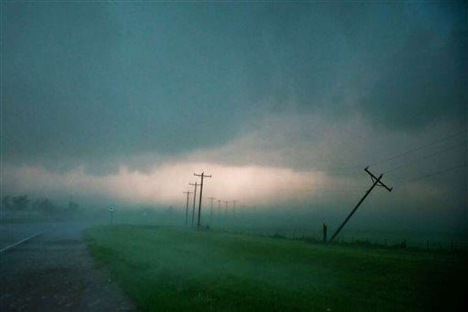 High winds snapped this power pole on from Highway 81 just south El Reno Okla. on Friday May 31, 2013. Tornadoes rolled in from the prairie and slammed Oklahoma City and its suburbs on Friday, killing a mother and baby and crumbling cars and tractor-trailers along a major interstate. (AP Photo/The World-Herald, Chris Machian) Photo: AP / OMAHA WORLD-HERALD