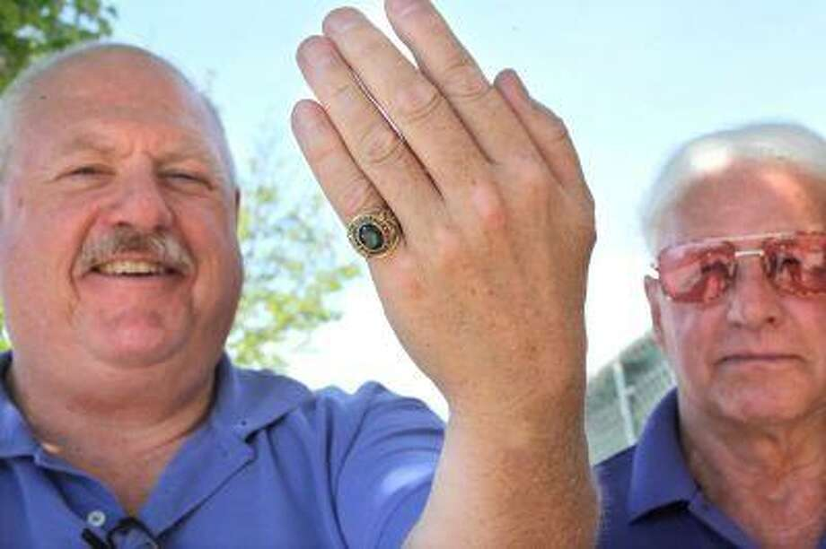 In this Thursday, June 20, 2013 photo, Mike Willsey poses with his ring, as Nelson Hoogerhyde stands in background, in Traverse City, Mich. Hoogerhyde found Willsey's 1971 Traverse City, Mich., High School class ring about 43 years ago, but only recently was able to discover the ring's owner and return it to Willsey. Photo: AP / Traverse City Record-Eagle