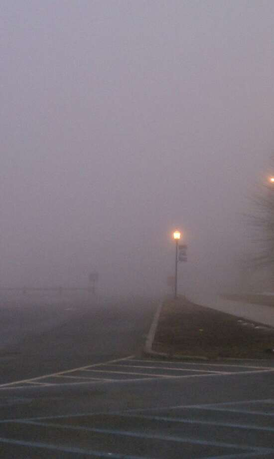 Fog can be seen in a parking lot in New Haven early Wednesday. A fog advisory remains effect until 10 a.m. Helen Bennett/Register