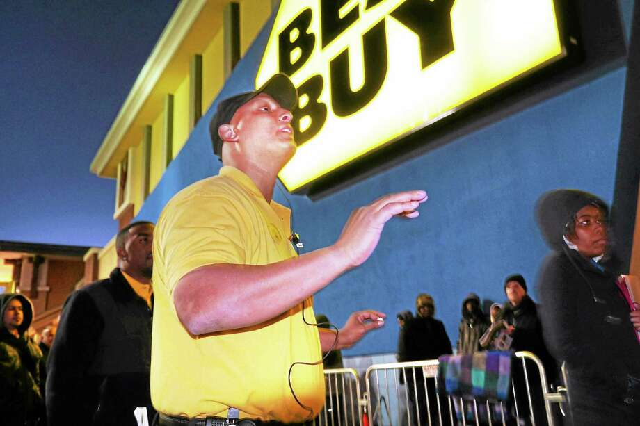 Richard Hill, manager of Best Buy in North Haven, instructs shoppers on how to find items they desire prior to the stores 6 p.m. opening Thursday. Photo: VM Williams — New Haven Register