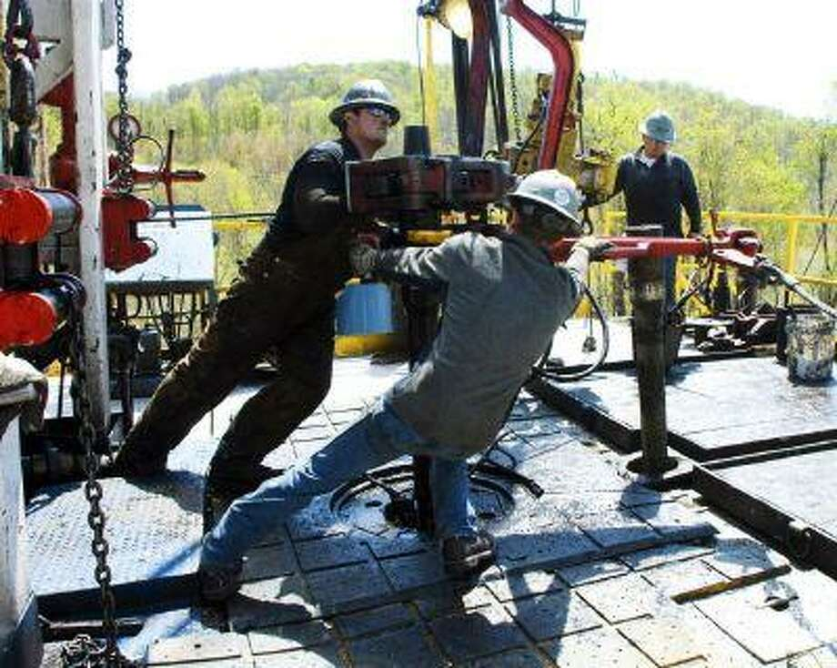 In April 2011, workers move a section of well casing into place at a Chesapeake Energy natural gas well site near Burlington, Pa., in Bradford County.