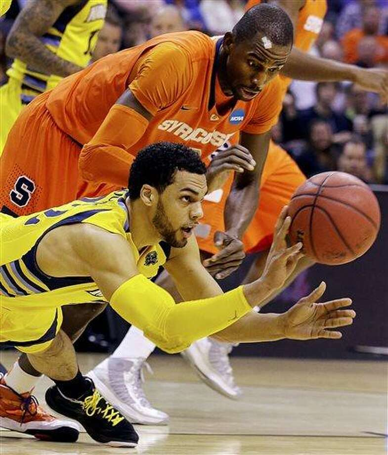 Marquette guard Trent Lockett (22) passes the ball away from Syracuse center Baye Keita (12) during the first half of the East Regional final in the NCAA men's college basketball tournament, Saturday, March 30, 2013, in Washington. (AP Photo/Alex Brandon) Photo: AP / AP