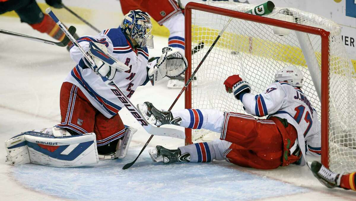 The New York Rangers' John Moore (17) slides past goalie Henrik Lundqvist (3) into the goal as they try to stop a Panthers shot during the second period of Wednesday's game in Sunrise, Fla.