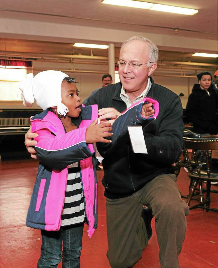 Knights of Columbus Supreme Knight Carl Anderson helps a child put on a new coat during the K of C Coats for Kids distribution held the day after Thanksgiving last year in Bridgeport. Photo: Contributed Photo   / (c)KNIGHTS OF COLUMBUS