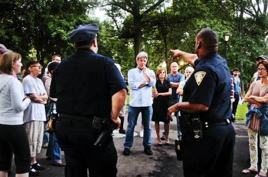 Melanie Stengel Register        Aldermanic candidate for the 8th Ward, Peter Webster, talks with New Haven police about concerns of residents in the Wooster Square area 7/26.  Police met with reidents who later accompanied the officers on their walking beat.