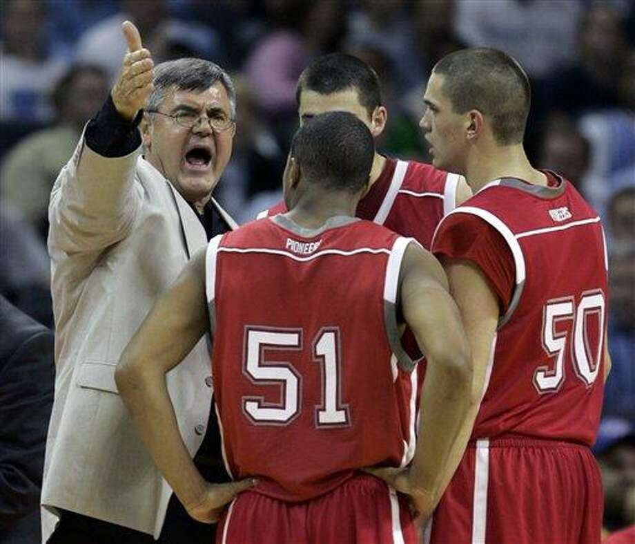Sacred Heart coach Dave Bike, left, talks to his team during the timeout in the second half of their 103-81 loss to North Carolina in the first round of a preseason National Invitational Tournament basketball game in Charlotte, N.C., Tuesday, Nov. 14, 2006. (AP Photo/Chuck Burton)