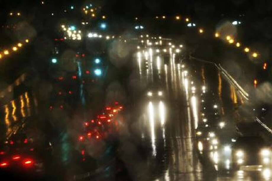 Reflected in the driver side mirror, motorists drive in the rain on Montrose Road in Rockville, Md., towards Interstate 270 out of Washington, Tuesday, Nov. 26, 2013, two days before the Thanksgiving holiday. (AP Photo/Charles Dharapak) Photo: AP / AP