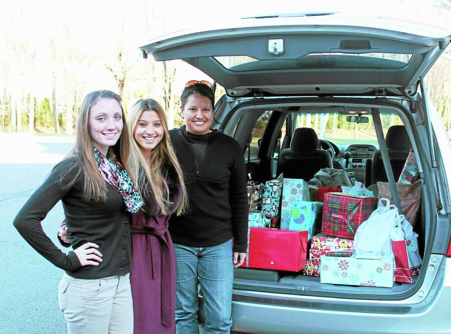 Contributed photo/Register. Antigone Curis, president of the Quinnipiac University Criminal Law Society, center, smiles with Shannon Haggerty, a shelter case manager, left, and Nadya Zawrocki, a resident support staff member, both of the Umbrella Center for Domestic Violence Services. Behind them is a van full of donations Curis collected for children at the shelter. Each child will receive two gifts from Quinnipiac law students this Christmas. Photo: Journal Register Co.