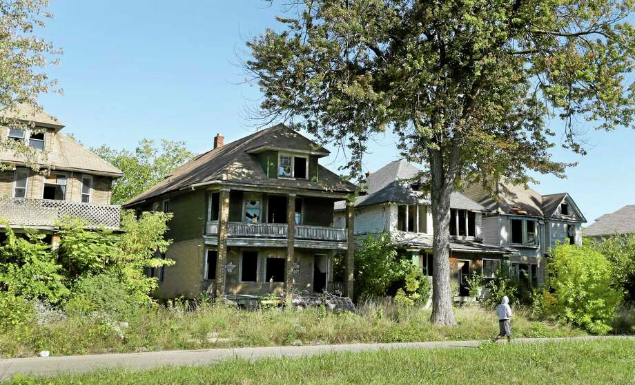 A young man walks in front of a row of abandoned houses in Detroit, Thursday, Sept. 26, 2013. Four of President Barack Obama's top advisers will converge on Detroit Friday to meet privately with state and local leaders about ways the federal government can help the bankrupt city short of a bailout. The White House said Thursday that top economic adviser Gene Sperling will join U.S. Attorney General Eric Holder, Transportation Secretary Anthony Foxx and HUD Secretary Shaun Donovan in the closed meeting. (AP Photo/Carlos Osorio) Photo: AP / AP