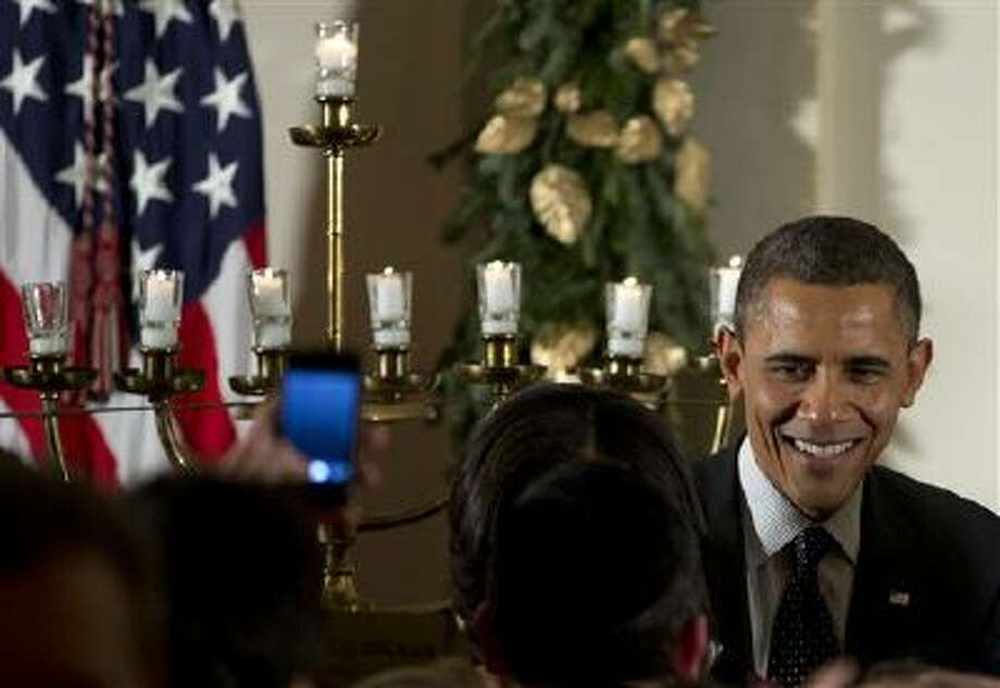 President Barack Obama greets people as he stands next to a lit Menorah during the Hanukkah reception in the Grand Foyer of the White House, Thursday, Dec. 13, 2012, in Washington. (AP Photo/Carolyn Kaster) Photo: AP / AP