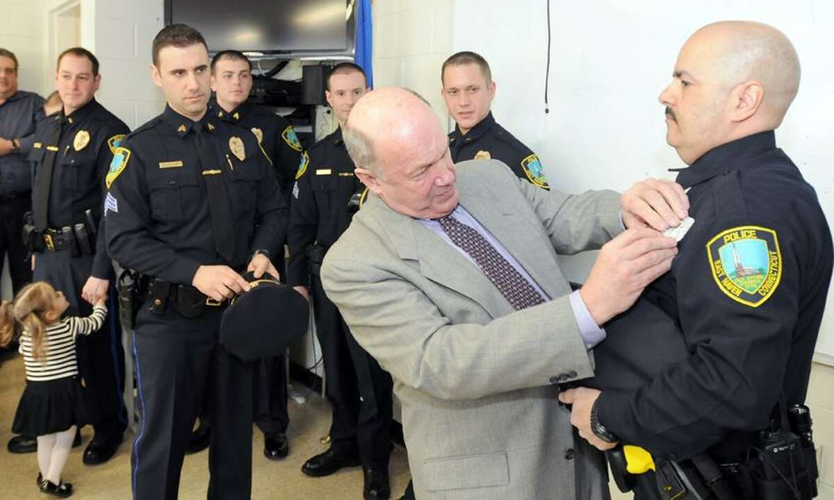 East Haven Police Chief Brent B. Larrabee pins a badge on officer Eduardo Diaz during a swearing in ceremony for promoted officers and new officers Thursday March 28, 2013 at East Haven Police Headquarters Thursday, March 28, 2013. Standing with Sgt. Ryabaruk from left are Lieutenant David Emerman, Sergeant Patrick Tracy, Sergeant Stephen Paulson, and Sergeant Justin Brochu. Officer Eduardo Diaz was a New Haven Police officer. Photo by Peter Hvizdak / New Haven Register