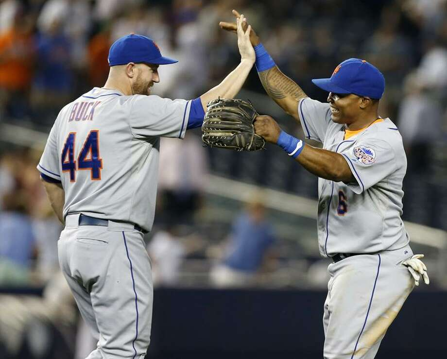 New York Mets right fielder Marlon Byrd, right, celebrates with designated-hitter John Buck (44) after the the Mets defeated the New York Yankees 3-1 to complete a four game sweep after an interleague baseball game series at Yankee Stadium in New York, Thursday, May 30, 2013. (AP Photo/Kathy Willens) Photo: AP / AP
