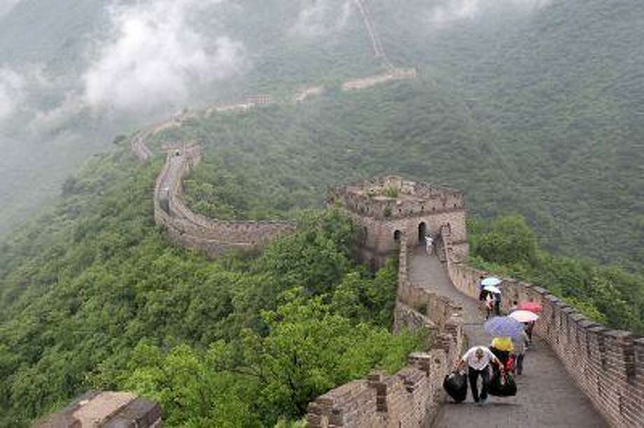 A trash collector passes tourists as he walks along the Great Wall of China at Mutianyu recently. Illustrates CHINA-QANDA (category f), by Lillian Cunningham, special to The Washington Post. Moved Sunday, July 28, 2013. Photo: THE WASHINGTON POST / THE WASHINGTON POST
