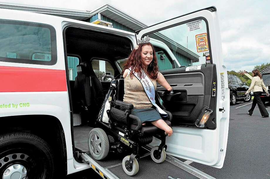 Ms. Wheelchair America Jennifer Lynn Adams tries out one of the MV-1 wheelchair-accessible taxis at Metro Taxi headquarters in West Haven Friday. Photo: Peter Casolino — New Haven Register