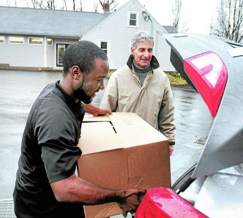 Homer Anthony, left, of Jordan Caterers loads Thanksgiving dinners into the trunk of Mark Farber's car in Cheshire Wednesday. Photo: Arnold Gold — New Haven Register