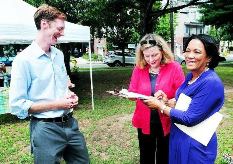 Arnold Gold/Register New Haven mayoral hopefuls Alderman Justin Elicker (left) and State Senator Toni Harp (right) cross paths Sunday at the farmer's market in New Haven's Edgewood Park. At center is State Rep. Patricia Dillon.