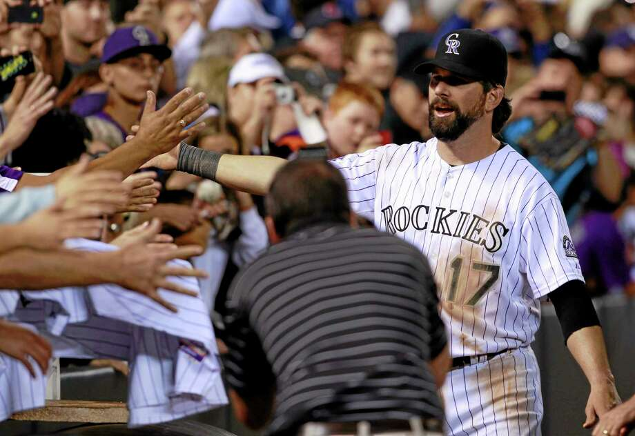 After playing in his final home game, Colorado Rockies first baseman Todd Helton greets fans as Helton circles the field after the Boston Red Sox's 15-5 victory on Wednesday. Helton will retire at season's end after playing 17 years at first base or he Rockies. Photo: David Zalubowski — The Associated Press   / AP