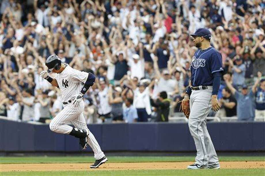 New York Yankees' Derek Jeter, left, rounds the bases after hitting a home run as Tampa Bay Rays first baseman James Loney looks on during a baseball game at Yankees Stadium, Sunday, July 28, 2013, in New York. (AP Photo/John Minchillo) Photo: AP / FR170537 AP