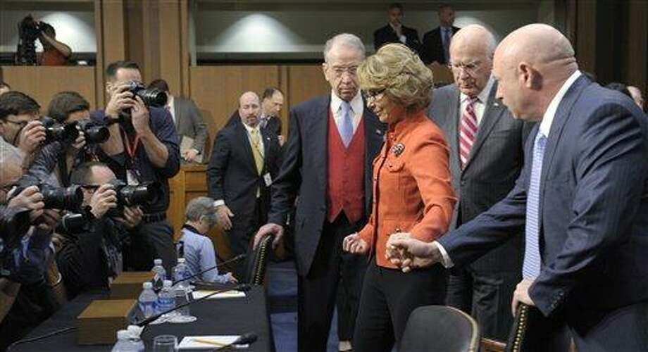 Former Arizona Rep. Gabrielle Giffords, center, who was seriously injured in the mass shooting that killed six people in Tucson, Ariz. two years ago, arrives with her husband Mark Kelly, right, on Capitol Hill in Washington, Wednesday, Jan. 30, 2013,  to give an opening statement before the Senate Judiciary Committee hearing on gun violence. Walking with Giffords is Senate Judiciary Committee Chairman Sen. Patrick Leahy, D-Vt., second from right, and the Committee's Ranking Republican, Sen. Chuck Grassley, R-Iowa. (AP Photo/Susan Walsh) Photo: AP / AP